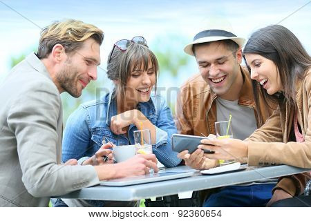 Young people at coffee shop looking at pictures on smartphone