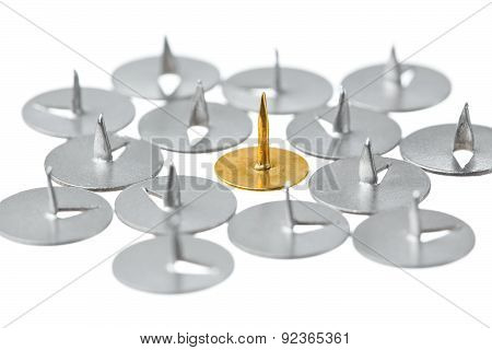 Golden thumbtack surround the usual on a white background