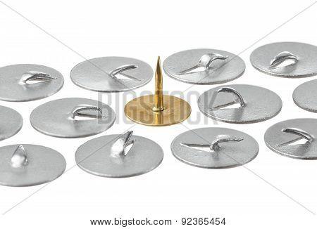 Among bent thumbtacks, one straight and gold