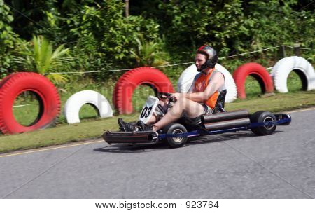 man racing a go cart at the race track poster