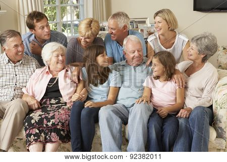 Large Family Group Sitting On Sofa Indoors