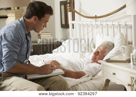 Doctor Talking With Senior Male Patient In Bed At Home