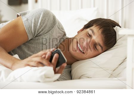 Teenage Boy In Bed At Home Texting On Mobile Phone