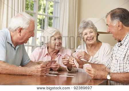 Group Of Senior Couples Enjoying Game Of Cards At Home