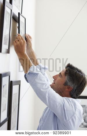 Man Hanging Picture Frames On Wall At Home
