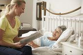 Adult Daughter Reading Newspaper To Senior Female Parent In Bed At Home poster