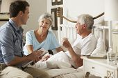 Doctor On Home Visit Discussing Health Of Senior Male Patient With Wife poster