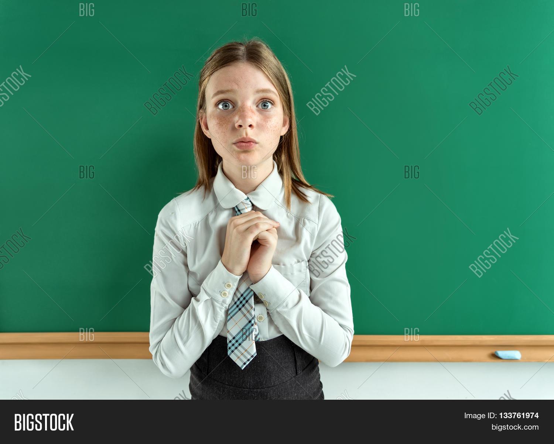 Cute Schoolgirl Near Blackboard With Folded Hands In Anticipation Of Something Photo Of Teen School