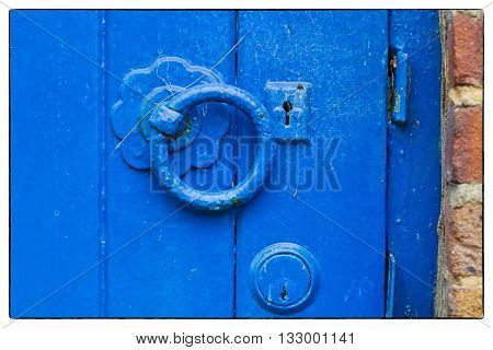 A metal blue painted latch on a blue painted wooden door. Vintage border