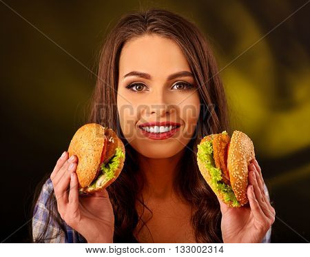 Happy girl holding two small fastfood hamburgers. Fastfood concept on green.