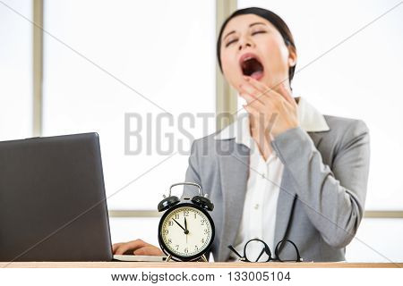 Tired Asian Businesswomen Yawing At Desk, Overtime And Overworked