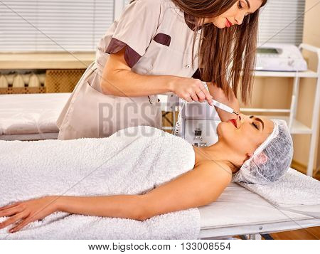 Young woman receiving electric galvanic face spa massage at beauty salon. Modern facial massage.