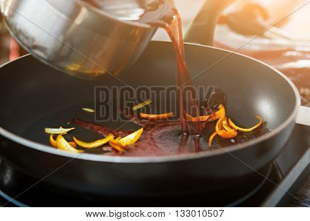 Liquid pouring on frying pan. Orange peel and red liquid. Preparing ingredients for special sauce. Wine mixed with orange skin.