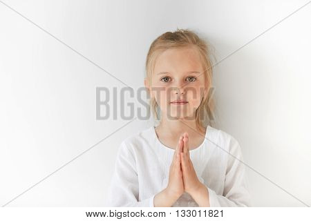 Little European Girl In White Clothes Praying And Looking Forward With Calm And Pretty Facial Expres
