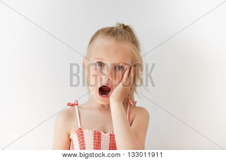 Blond European Girl Staring At The Camera In White Background. Amazed Kid Opening Her Mouth In Surpr