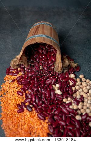 Group of beans lentils and chick-pea in wooden cup on black background. beans assortment. Beans variety closeup