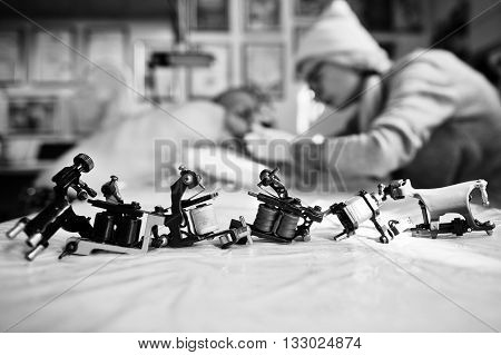 Set Of Different Machines For Tattoo Background Tattoo Master At Work. Black And White Photo