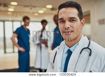 Male Doctor With Colleagues In Background