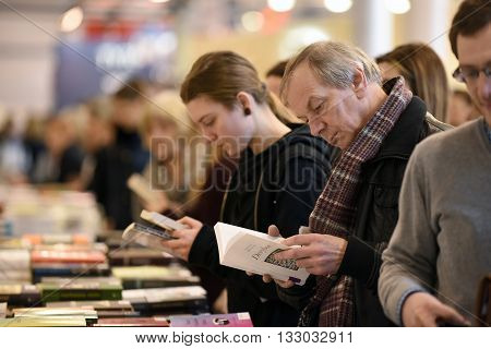 VILNIUS - FEBRUARY 26: Many people choose books at the indoor book market on February 26 2016 in Vilnius Lithuania. Vilnius is the capital of Lithuania and its largest city.