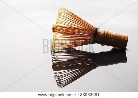 A chasen - special bamboo matcha tea whisk. Macro with reflection of the object.