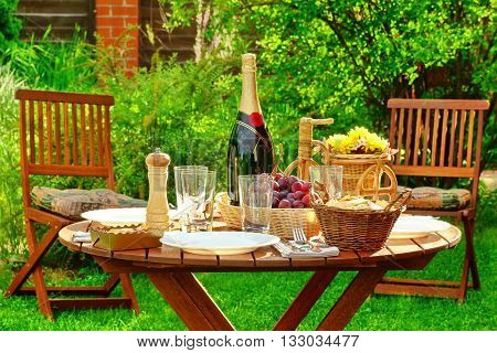 Outdoor Lunch Table With Bottle Of Wine On The Backyard