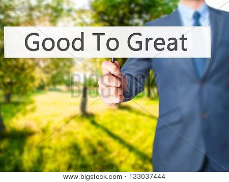 Good To Great - Businessman Hand Holding Sign