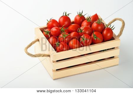 Red Cherry Tomatoes In Wooden Box Over White