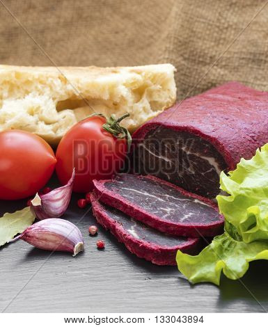 jerky in spices with bread and vegetables