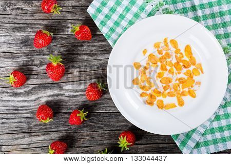 Corn flakes with milk and strawberry in a white dish on an old rustic table studio lightrs