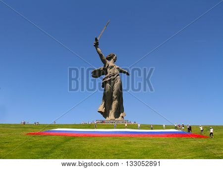 VOLGOGRAD RUSSIA - JUNE 12 2013: Activists unfurl a large Russian flag in Day of Russia at the foot of the monument of Motherland Calls on Mamaev hill in Volgograd