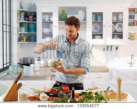 Casual man preparing salad at home in kitchen.