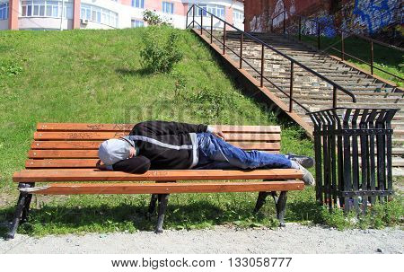 Drank Man Rests On A Bench In Park