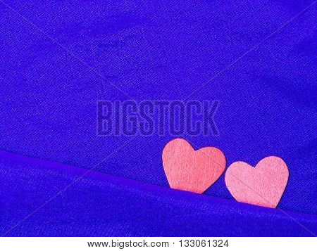 Valentines day background with red hearts on blue fabric. Love and Valentine concept.