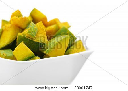 Organic sliced Indian Mango (Mangifera indica), seasoned with turmeric powder and salt in white bowl. Isolated on white background. Front view.