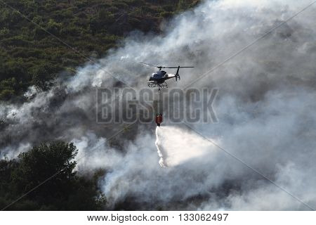 a fire helicopter engaged in fire fighting a forest fire