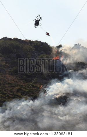 Emergency summer fires - helicopter involved in fire fighting a forest fire