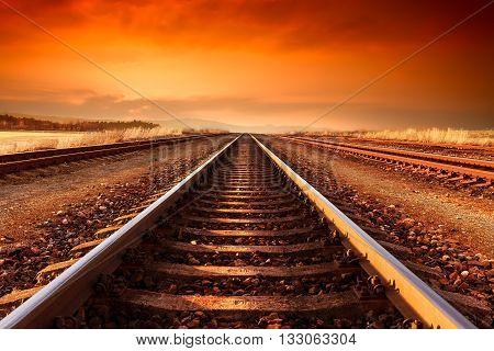 Train tracks goes to horizon in orange majestic sunset.