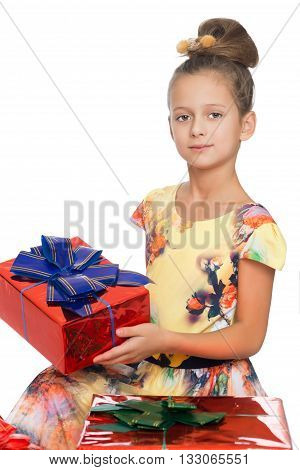 Dressy girl children with beautiful hair on your head holds in his hands a beautifully wrapped box tied with a blue bow. Close-up - Isolated on white background