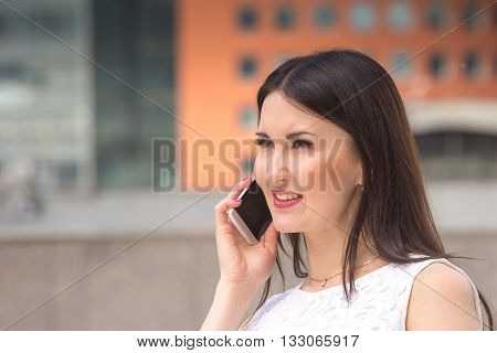 Pretty woman using mobile phone on urban background