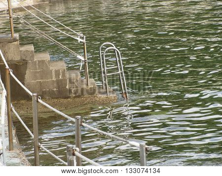 Ladder descending into the sea water . Tuscany Italy