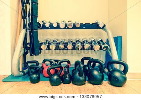Gym interior with equipment - Objects for crossfit training - Healthy lifestyle addiction concept - Focus on center dumbbells - Vintage editing