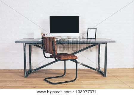 Front view of designer desk with blank computer display frames and other items with brown chair next to it. Wooden floor and white brick wall background. Mock up