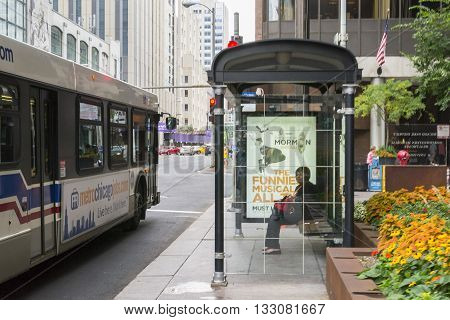 CHICAGO,USA-AUGUST 12,2013:A woman waiting a bus in a Chicago bus stop during a normal day of summer.
