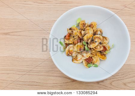 delicious dish of spicy pasta with shellfish and Sunflower sprout on wooden table