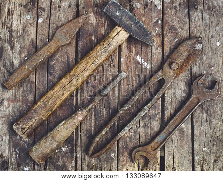 Old rusty tools lying on a wooden table. Hammer chisel metal scissors wrench chisel.