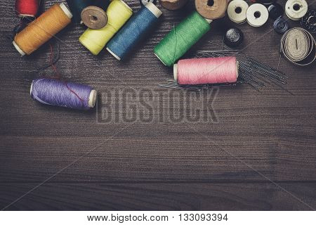 threads buttons and needles on the wooden table