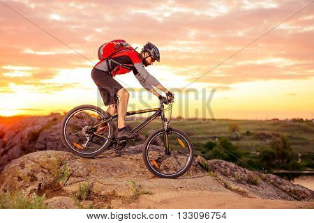 Cyclist Riding the Bike Down Hill on the Mountain Rocky Trail at Sunset. Extreme Sports poster