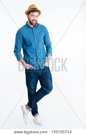 Handsome casual man smiling standing hands in his pockets with legs crossed isolated on the white background