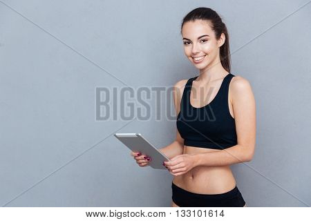 Beautiful young sportswoman using pc tablet and looking at camera isolated on grey background