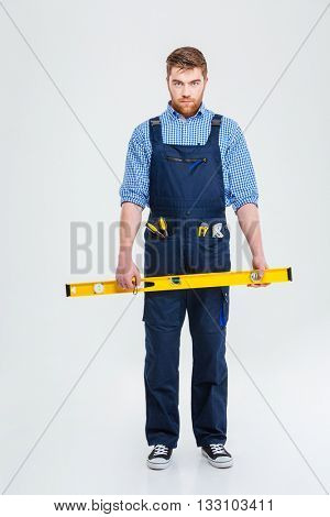 Full length portrait of a serious male builder holding waterpas and looking at camera isolated on a white background